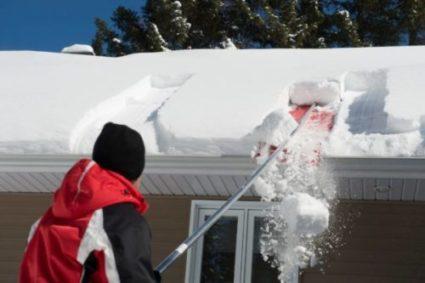 un homme déneige son toit avec la pelle à déneigement de toiture Snowpeeler